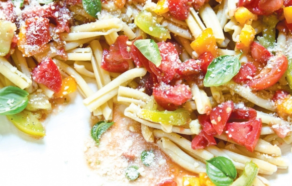 uncooked marinated tomatoes over pasta
